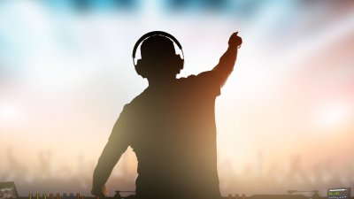 DJ usando fone de ouvido visto de costas, tocando e apontando para a platéia ao fundo.