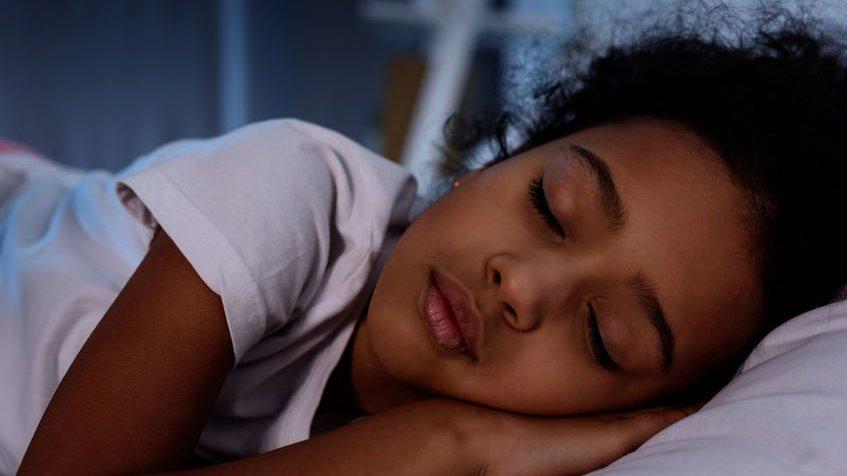 Criança negra dormindo na cama em casa.