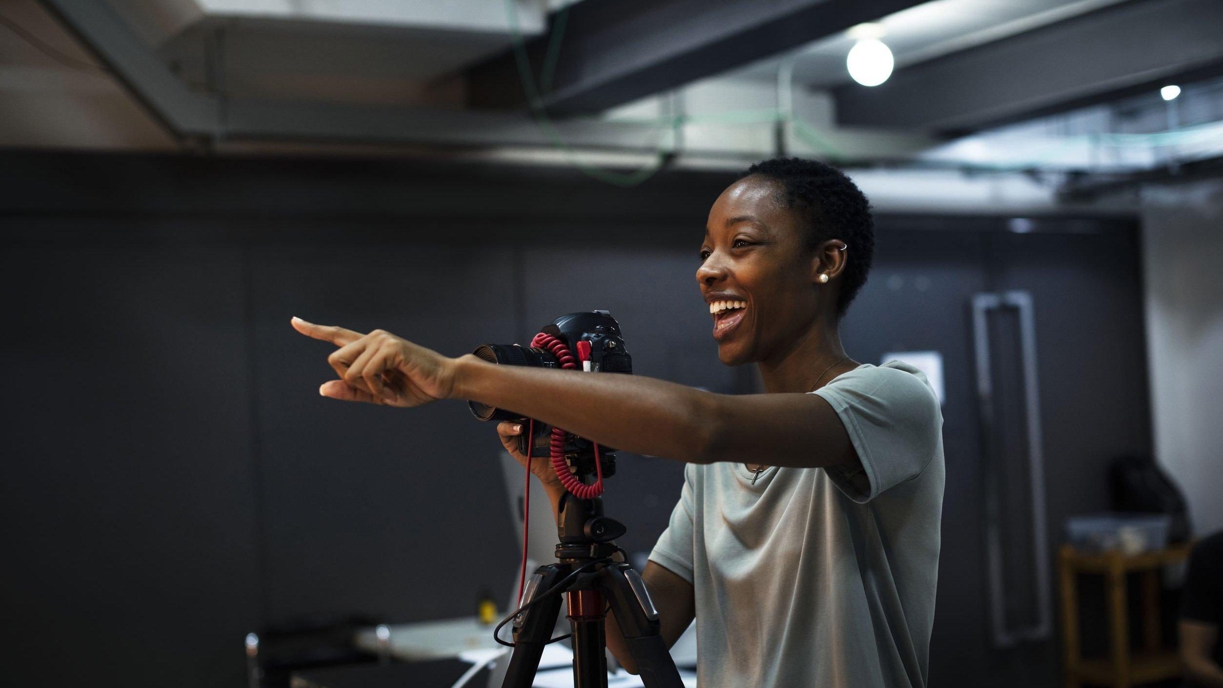 Mulher negra atrás de uma câmera, com o braço esquerdo apontado para frente, e expressão sorridente.