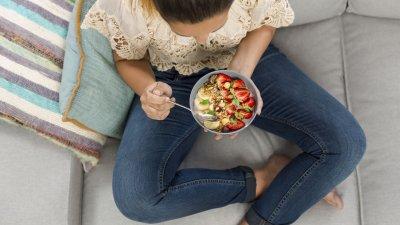 Mulher sentada no sofá comendo um pote de frutas