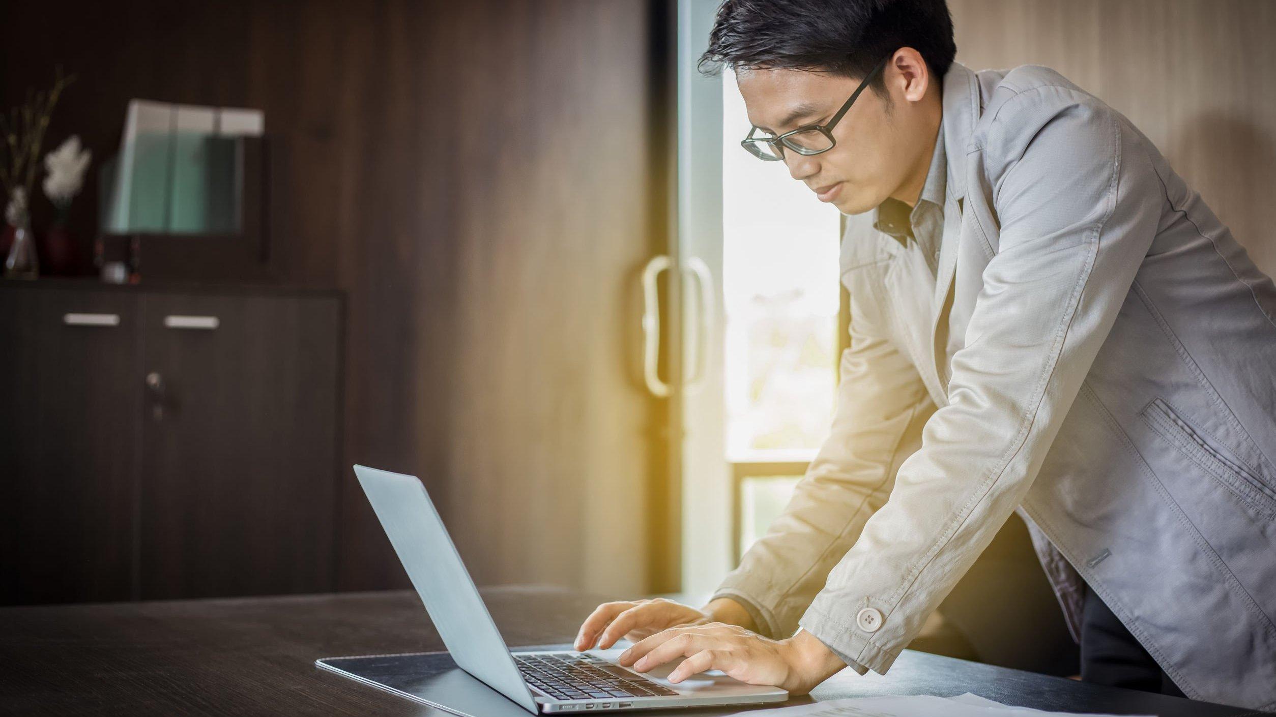 Homem de pé mexe em computador que está sobre uma mesa