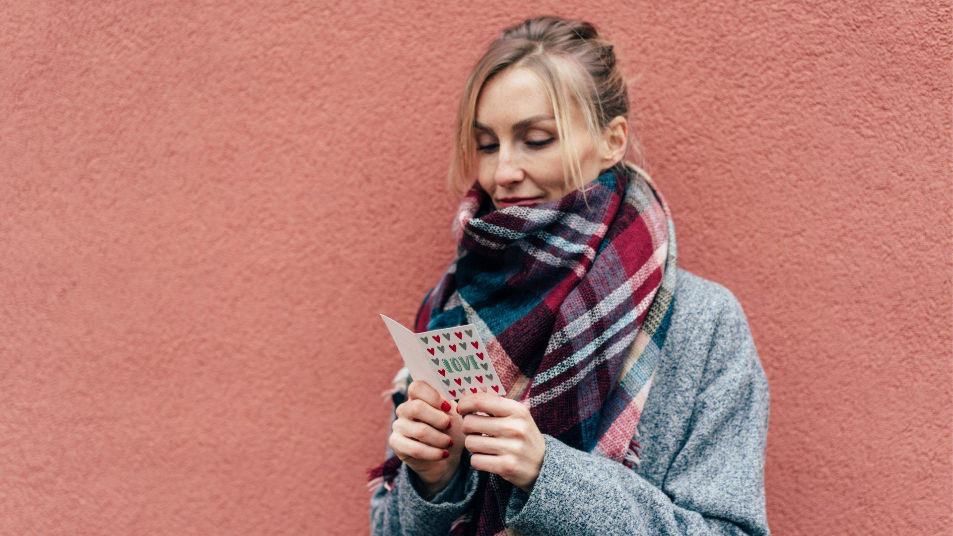 Mulher sorrindo enquanto lê uma carta romântica