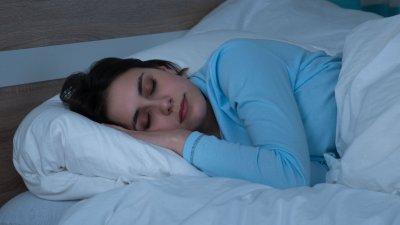 Mulher deitada na cama, dormindo.