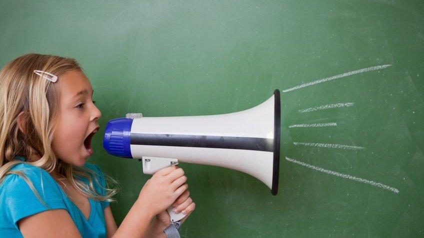 Uma menina gritando em um megafone na frente do quadro-negro