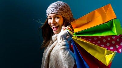 Mulher com roupas de frio sorrindo e segurando sacolas de compras