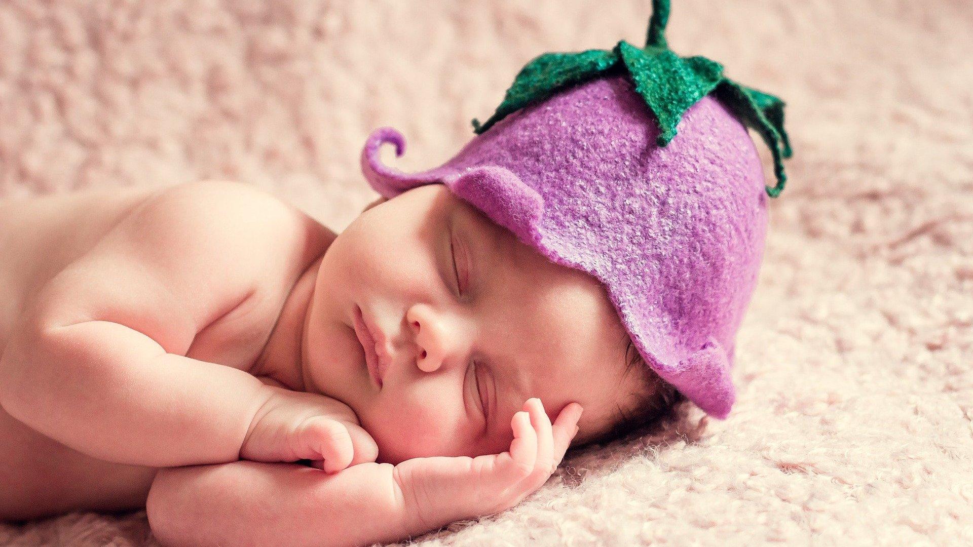 Bebê deitado com chapéu de uva