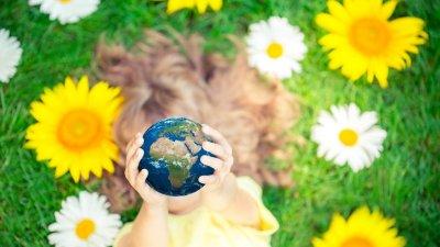 Menina deitada em grama, segurando uma miniatura do globo terrestre para o alto, cobrindo seu rosto.