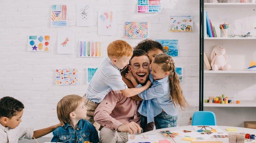 Professor com crianças em sala de aula sorrindo