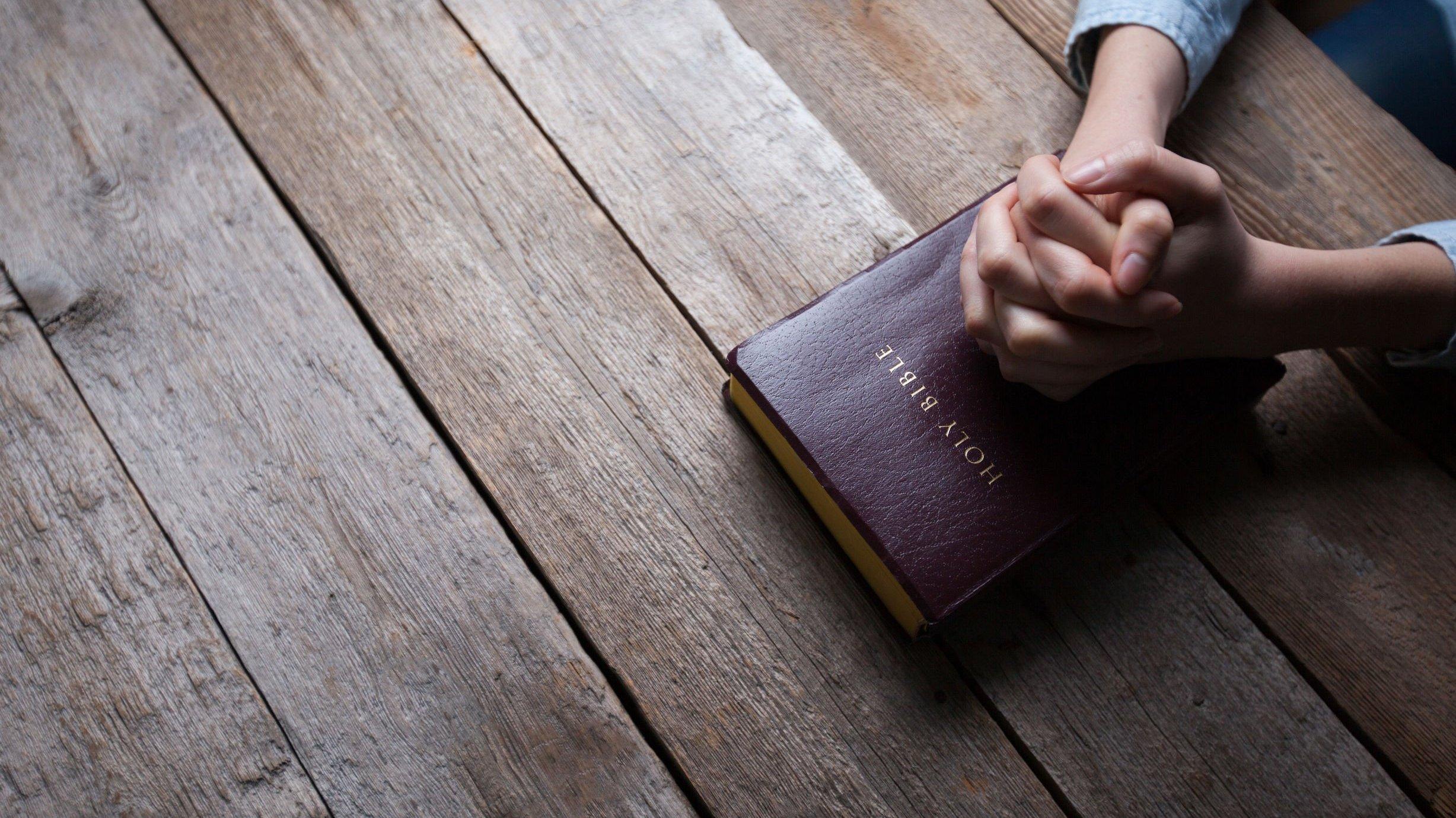 Mãos sobre bíblia sagrada em cima de superfície de madeira.