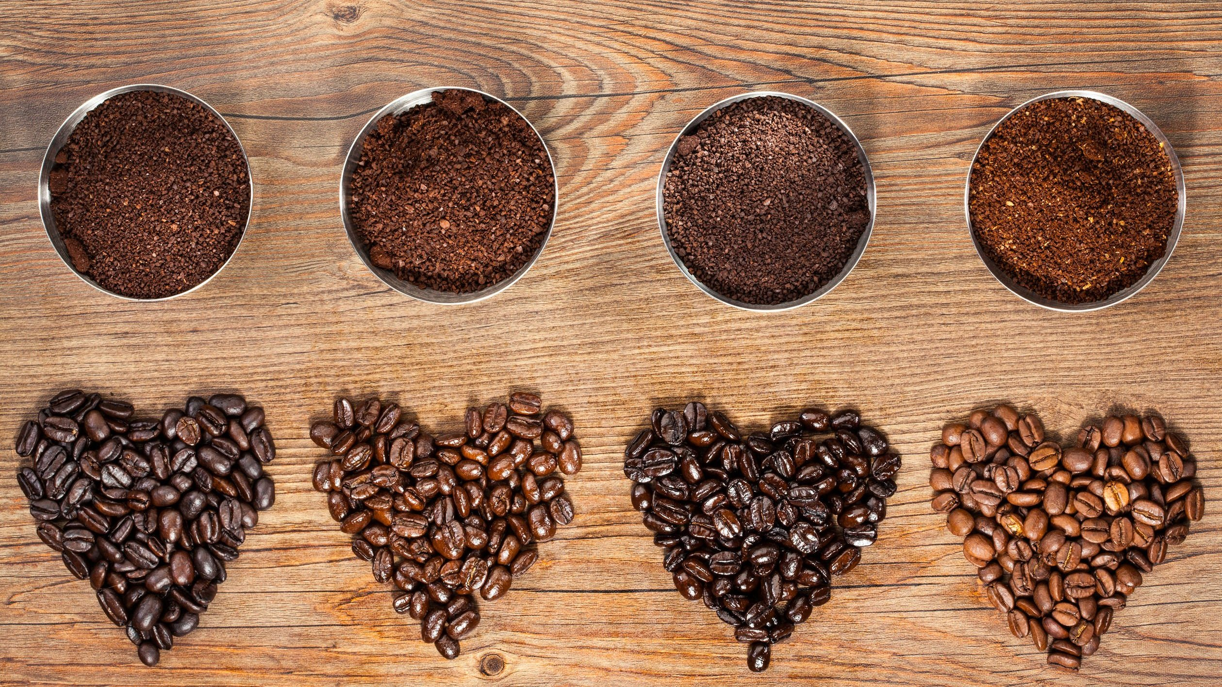 Grãos de café em formato de coração e grãos moídos.