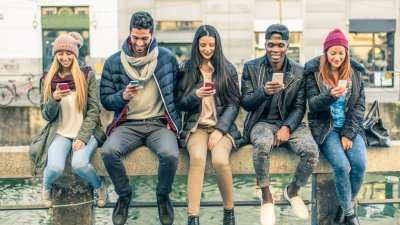 Amigos encostados em muro todos mexendo em seus celulares