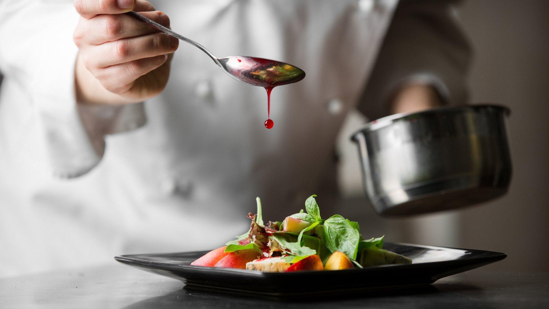 Cozinheira com uma colher terminando um prato