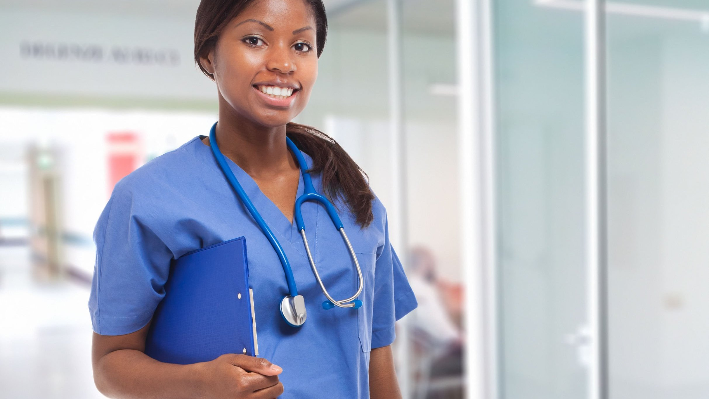 Enfermeira sorri e segura prancheta azul.