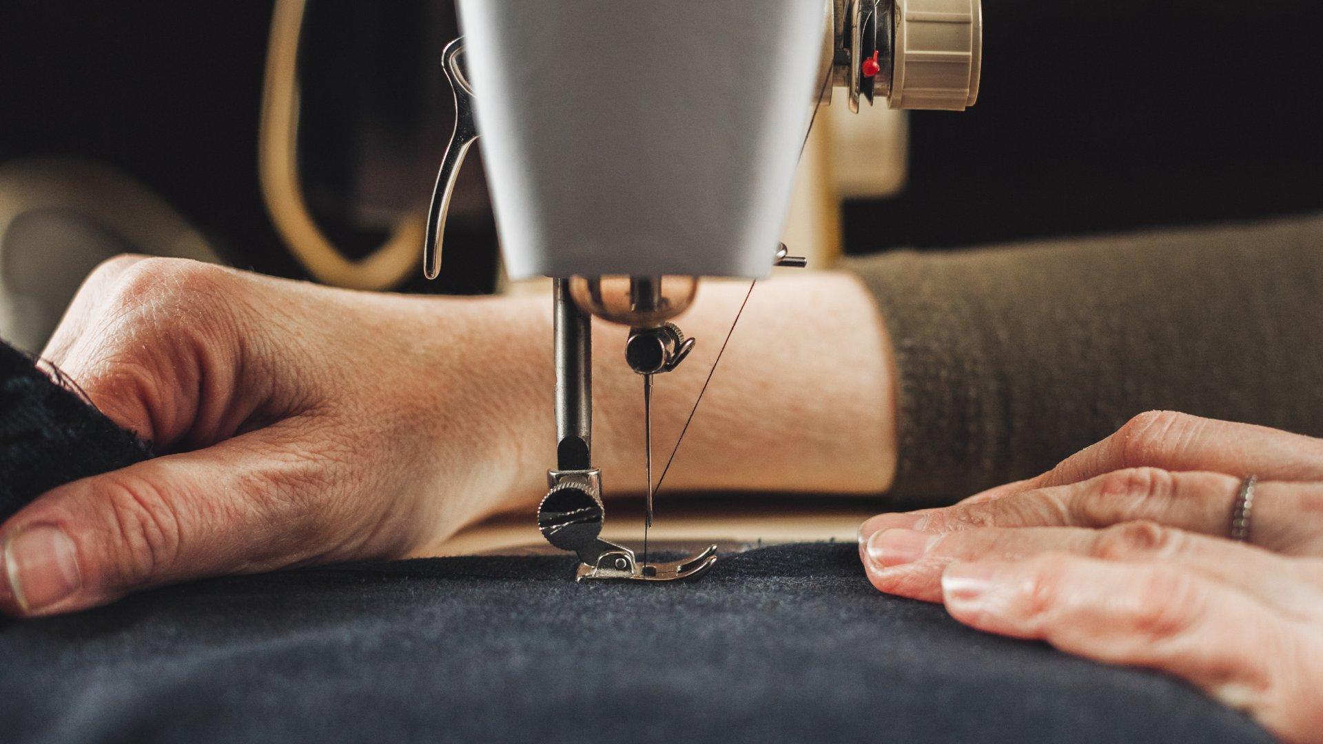 Pessoa costurando pano em máquina de costura