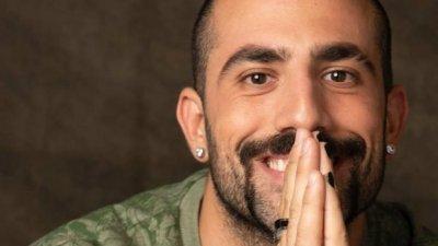 Homem sorrindo com as mãos juntas em sua boca