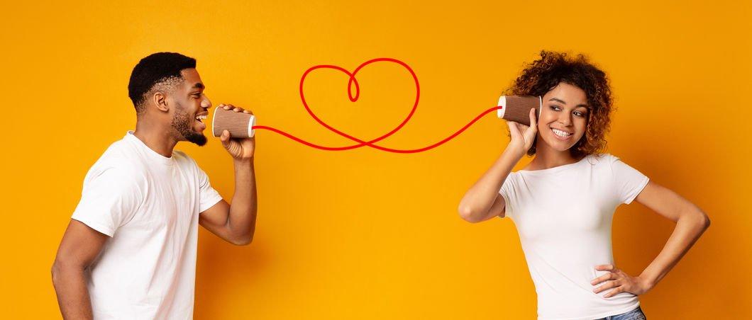 Homem falando em telefone sem fio com mulher e coração no meio