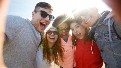 Amigos abraçados rindo e tirando uma selfie