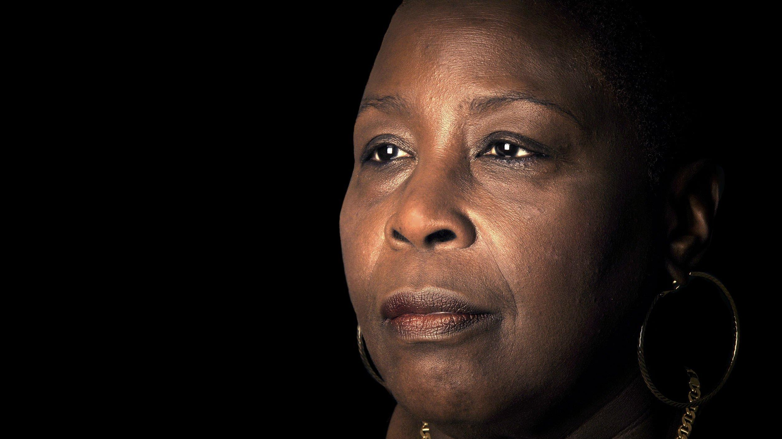 Mulher negra olhando para o lado com olhar de tristeza