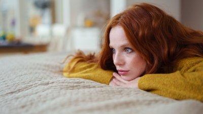 Mulher olhando para frente séria deitada na cama de bruços