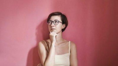 Mulher usando óculos com sua mão no queixo pensando