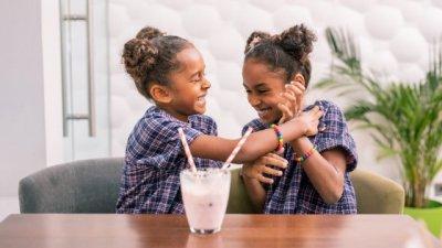 Duas irmãs sorrindo sentadas em uma mesa com um milkshake