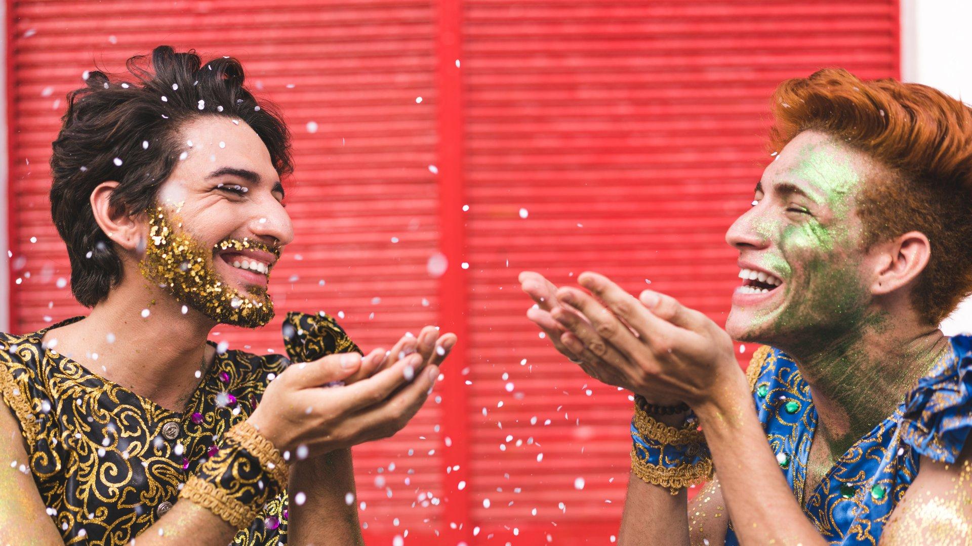 Dois homens sorrindo enquanto jogam confete para o alto