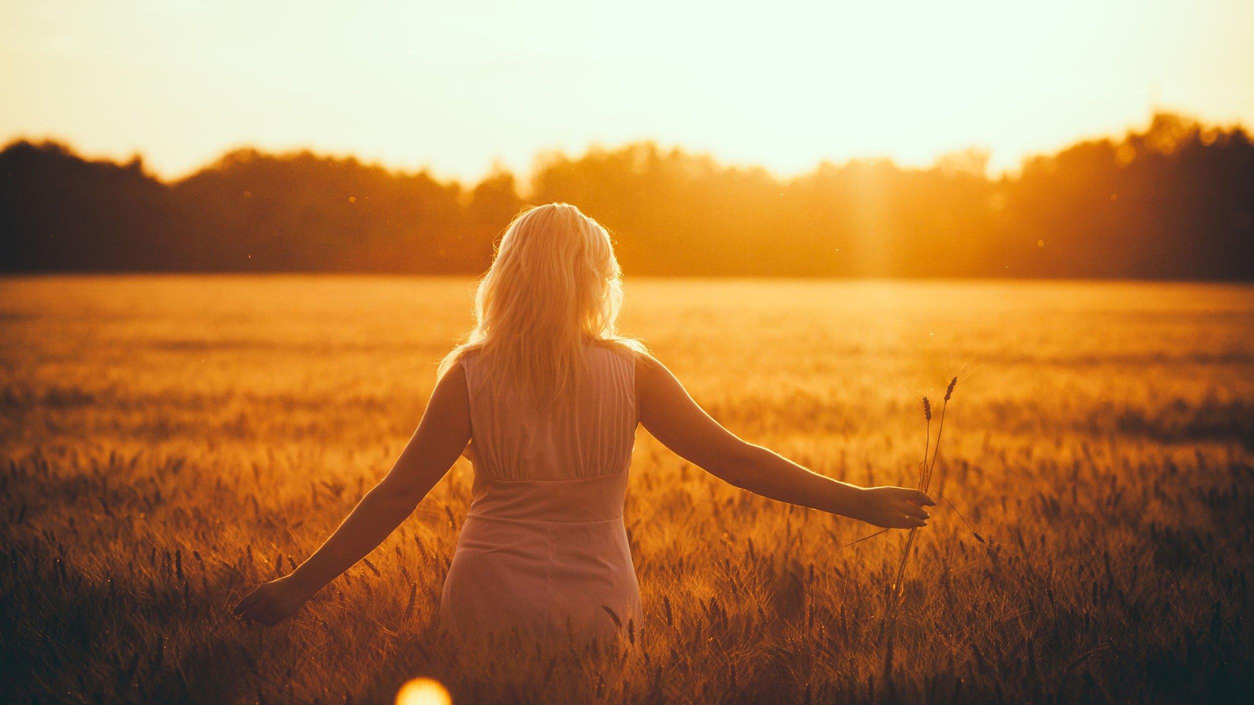 Mulher branca e loira de costas num campo durante o pôr-do-sol.