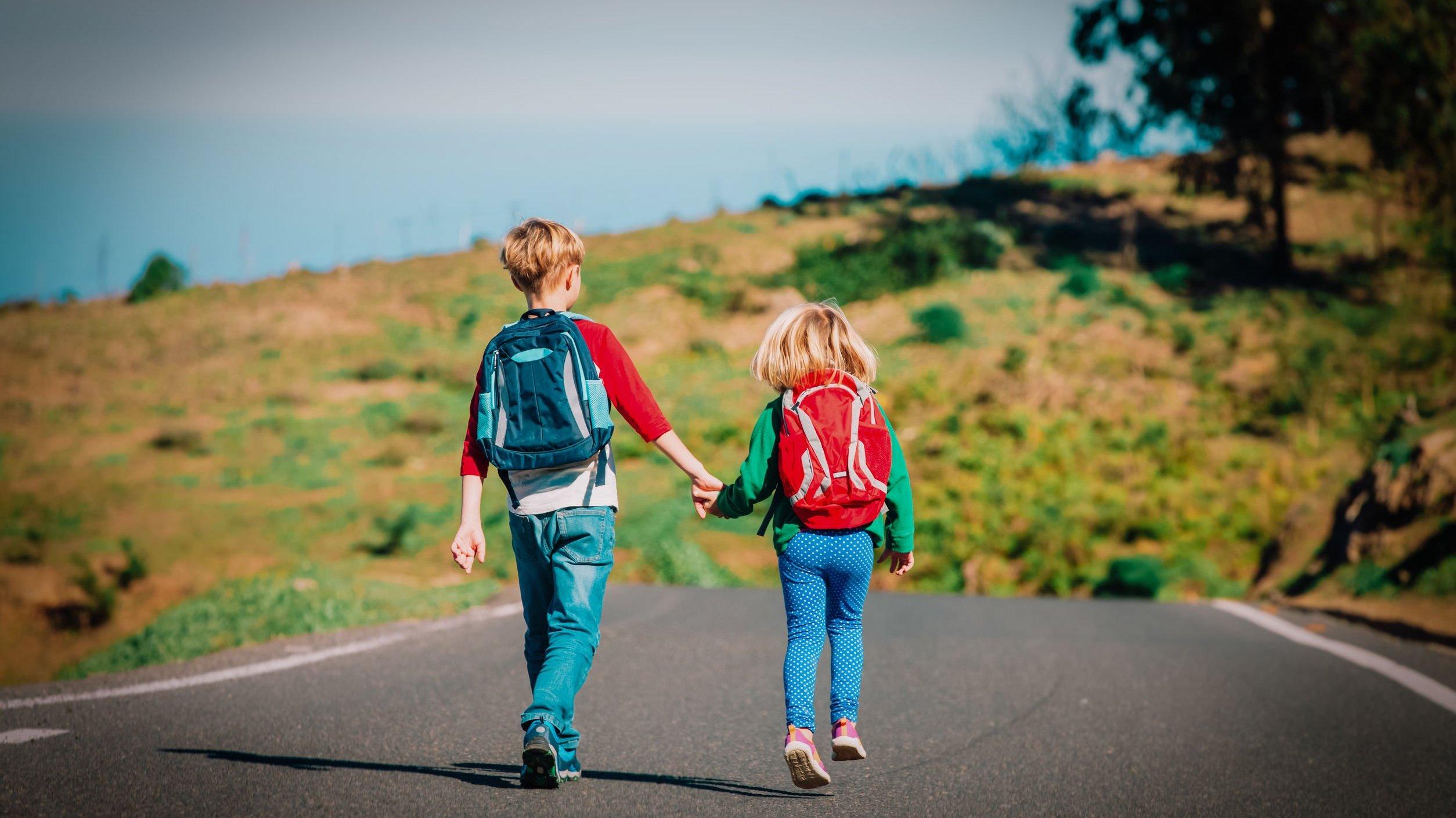 Menino e menina brancos e loiros andando de mãos dadas numa estrada com mochila nas costas