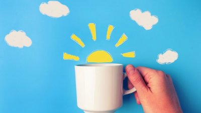 Mão segurando xícara com sol em desenho atrás