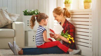 Sobrinha sentada no colo da tia com cartão e flores sorrindo