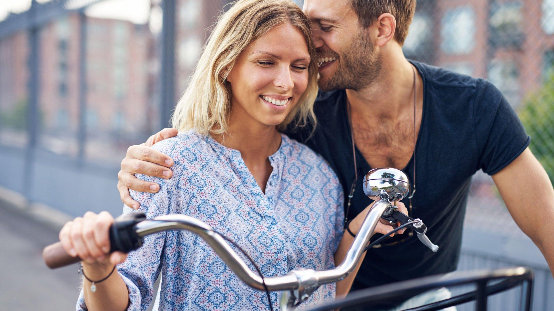 Casal sorridente andando de bicicleta