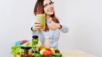 Mulher de óculos, sorrindo segurando copo de suco verde