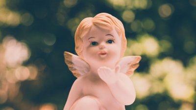 Pequena estátua de anjo soltando beijo com a mão