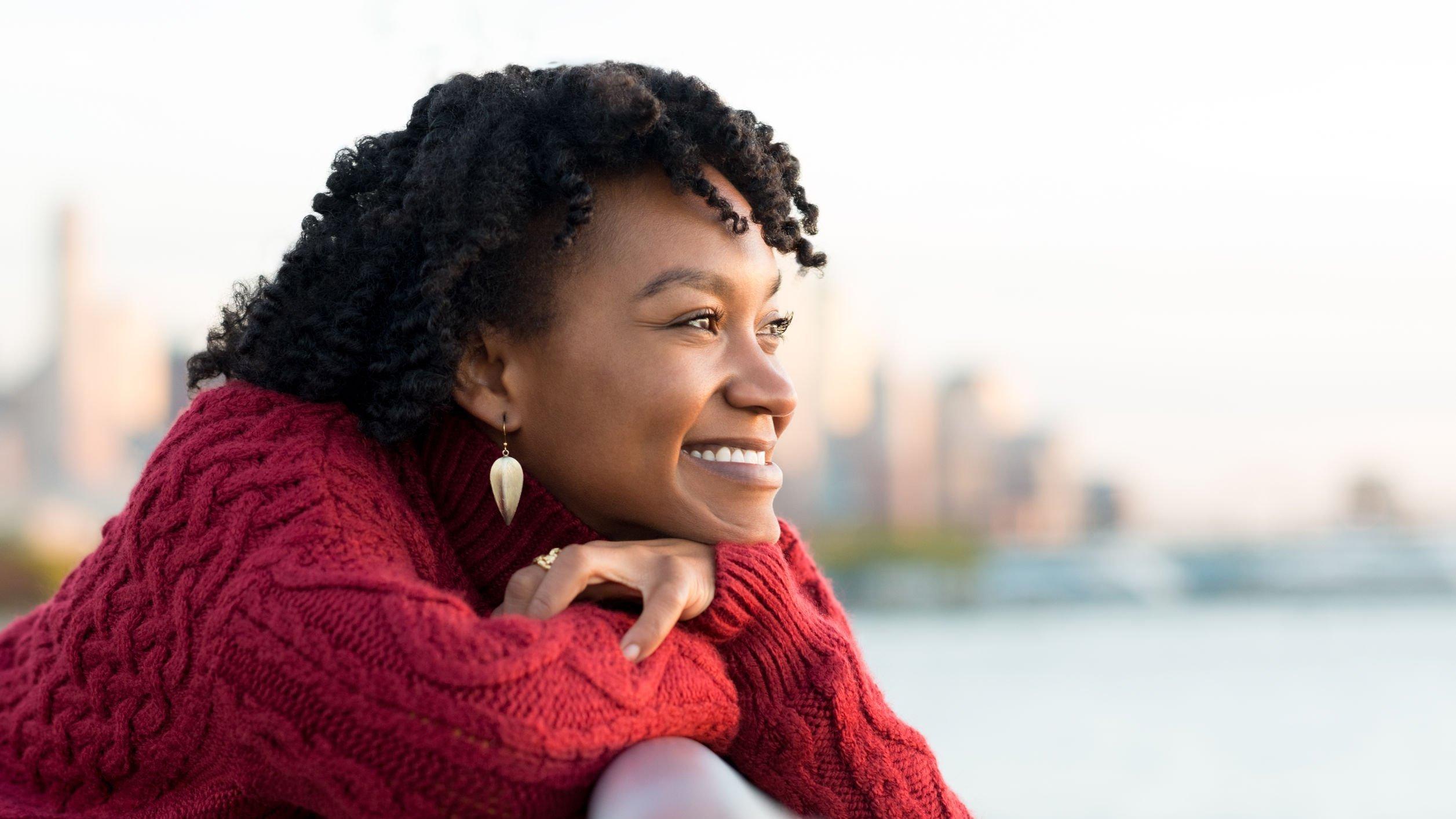 Mulher apoiada ao lado do mar sorrindo