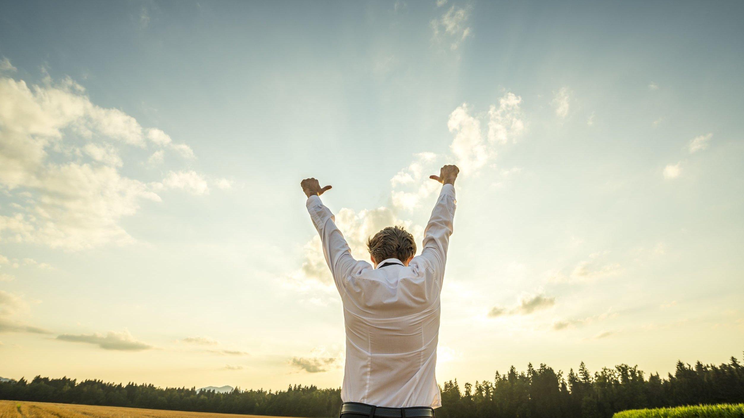 Homem branco de costas num campo com os polegares e braços levantados.