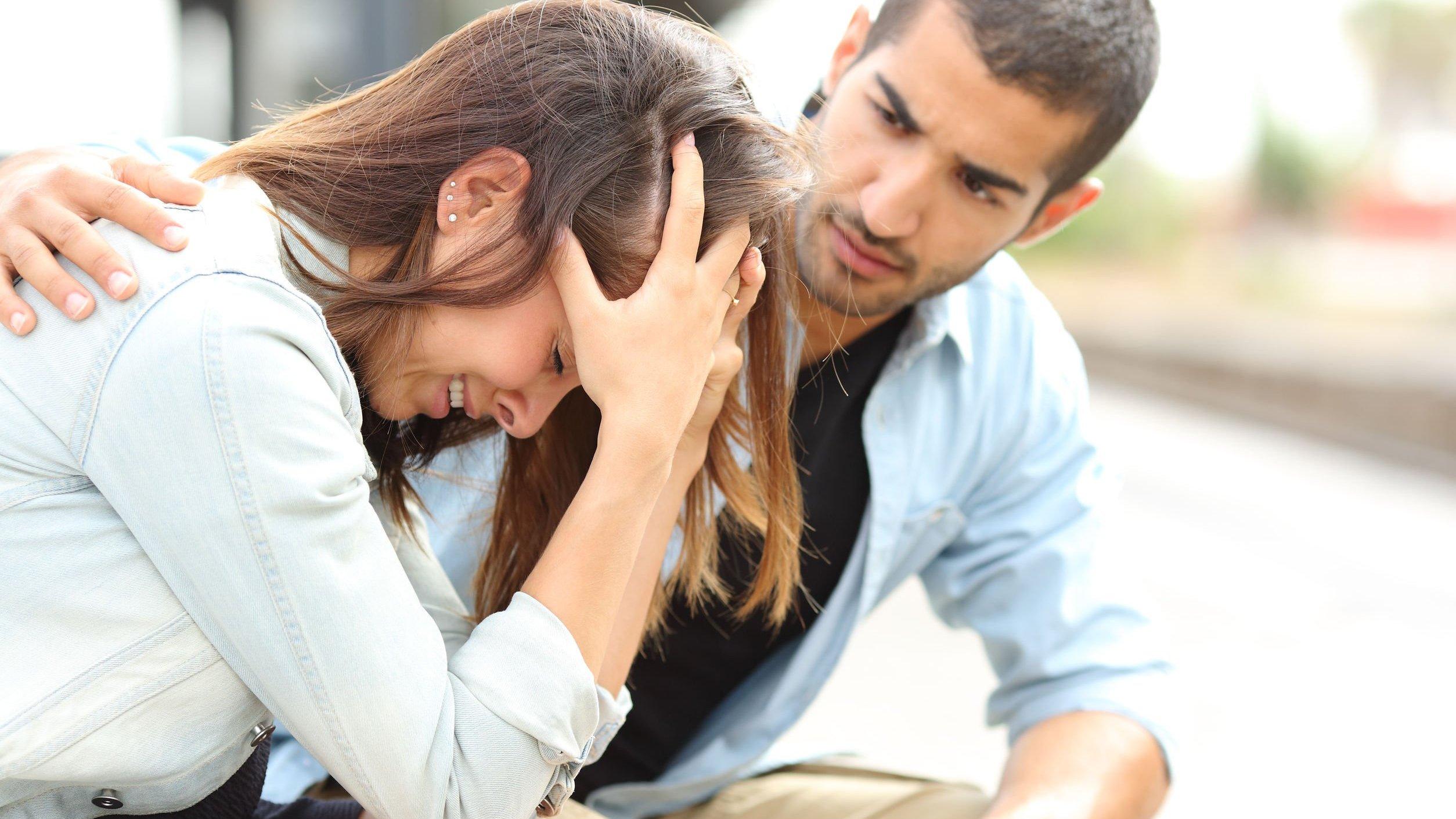 Mulher chorando com mãos na cabeça e homem tentando consolar