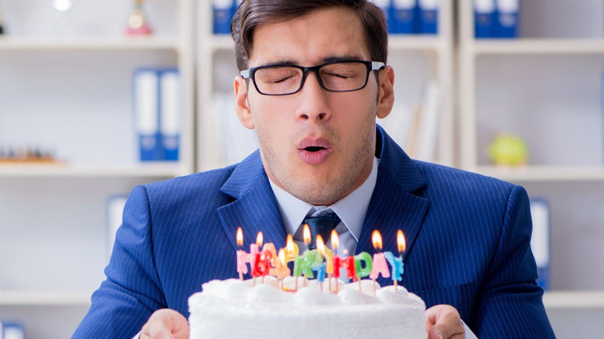 Homem assoprando velas do bolo.