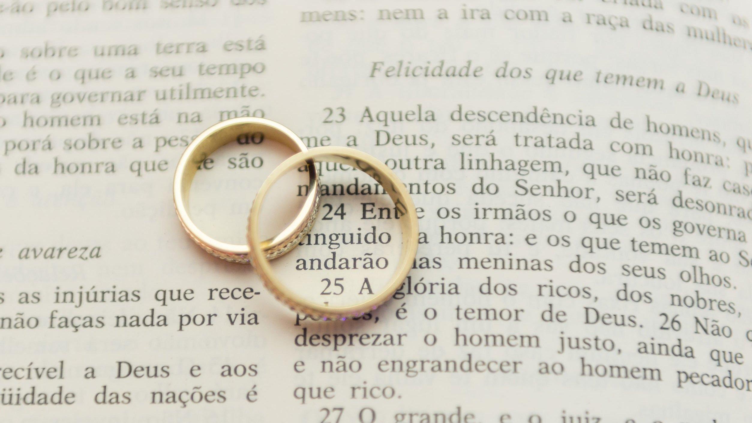 Alianças de casamento sobre bíblia aberta.