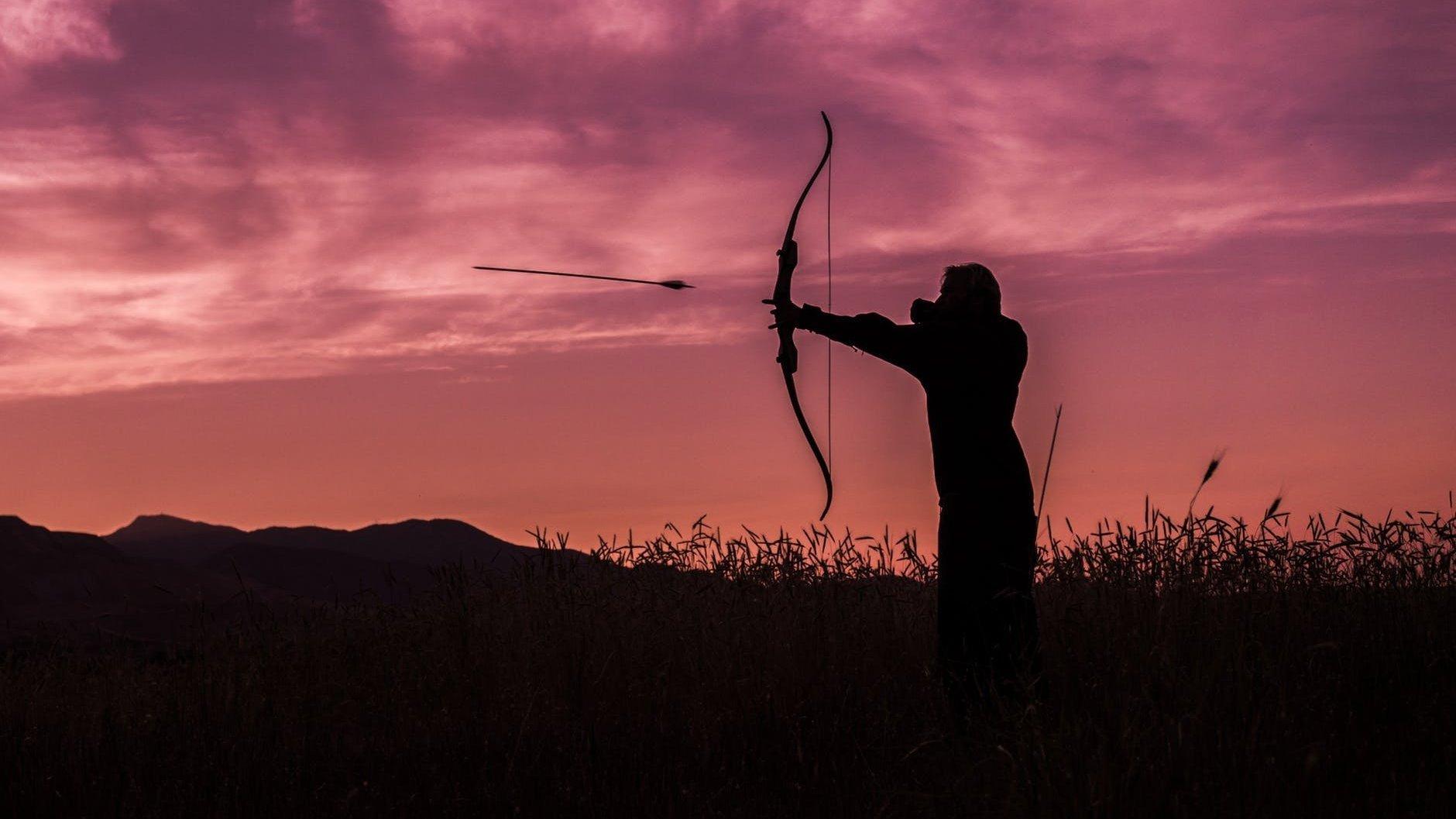 Silhueta de pessoa usando arco e flecha