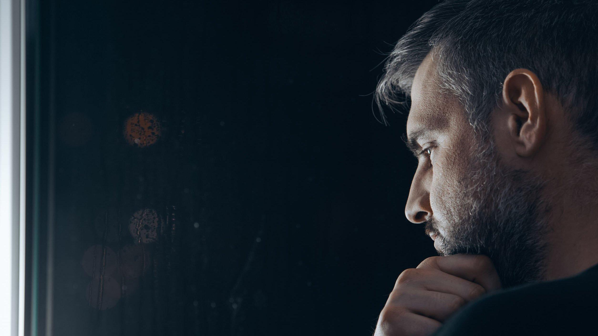 Homem refletindo em um fundo escuro.