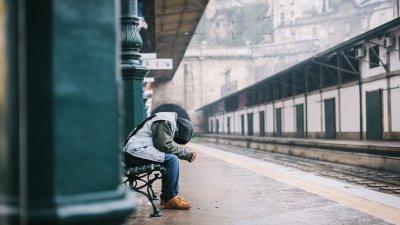 Pessoa vestindo capuz e sentada em estação de trem, segurando as duas mãos com a cabeça baixa.