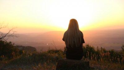 Mulher sentada no topo de uma montanha, de costas, observando o pôr do sol.