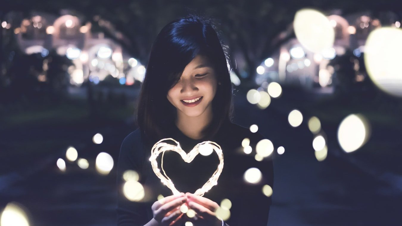 Mulher sorri enquanto segura um coração feito de luz, e olha para ele.