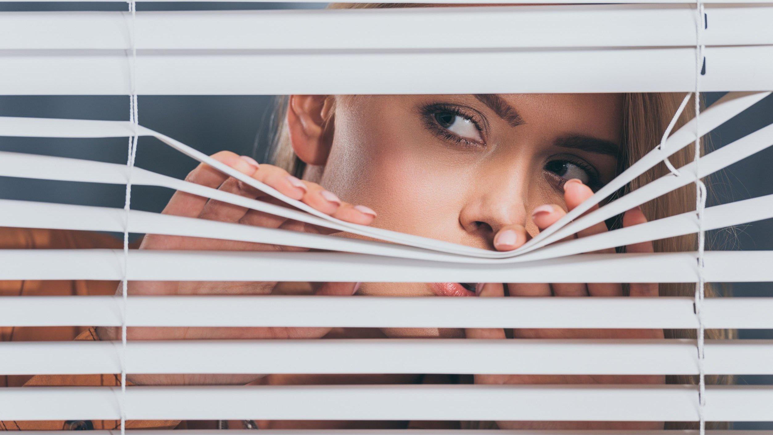 Mulher espiando por uma fresta na janela.