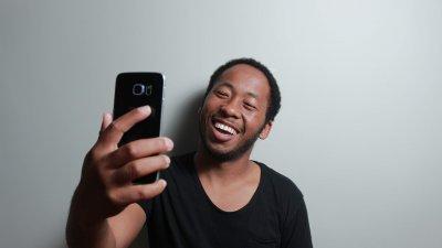 Homem em frente a parede branca sorrindo para uma selfie