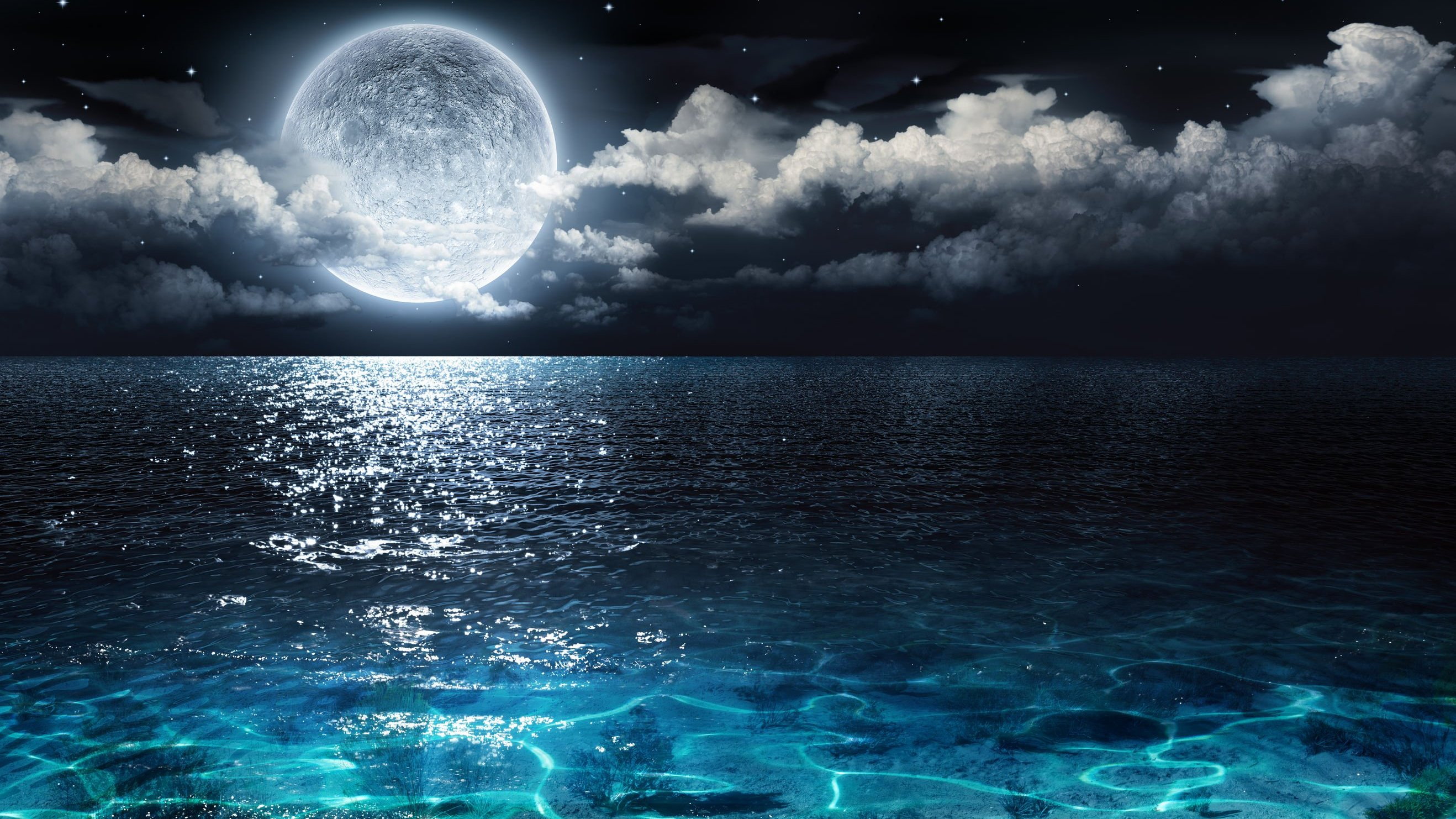 Céu estrelado e reflexo da lua no mar.