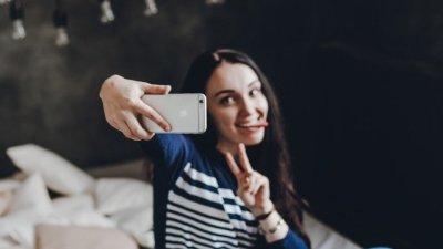 Mulher tirando selfie com a língua para fora
