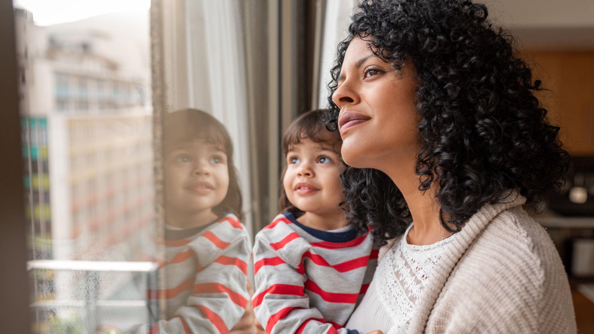 Mãe segurando sua filha no colo ao lado de uma janela