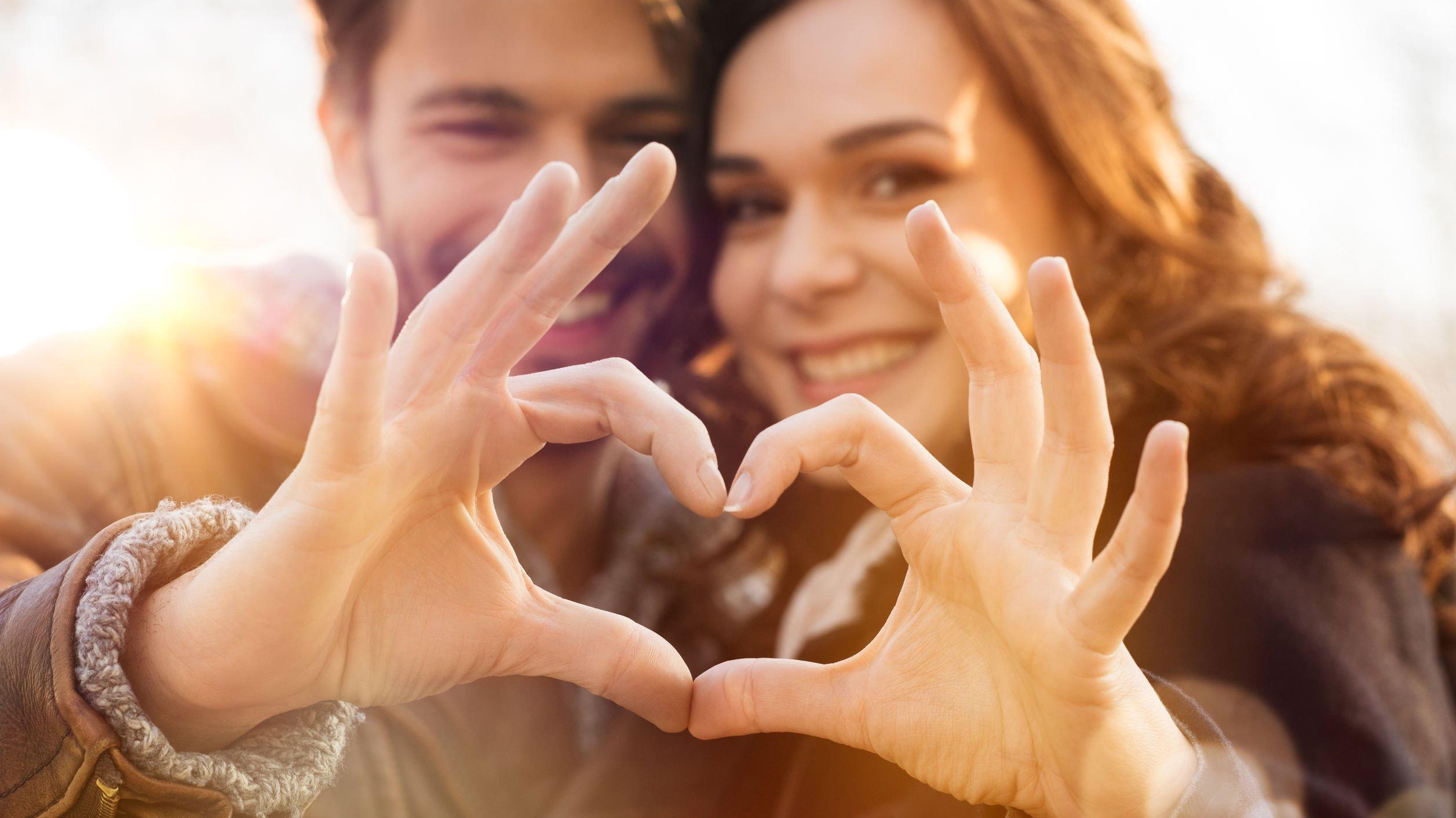 Foto de casal formando um coração com as mãos
