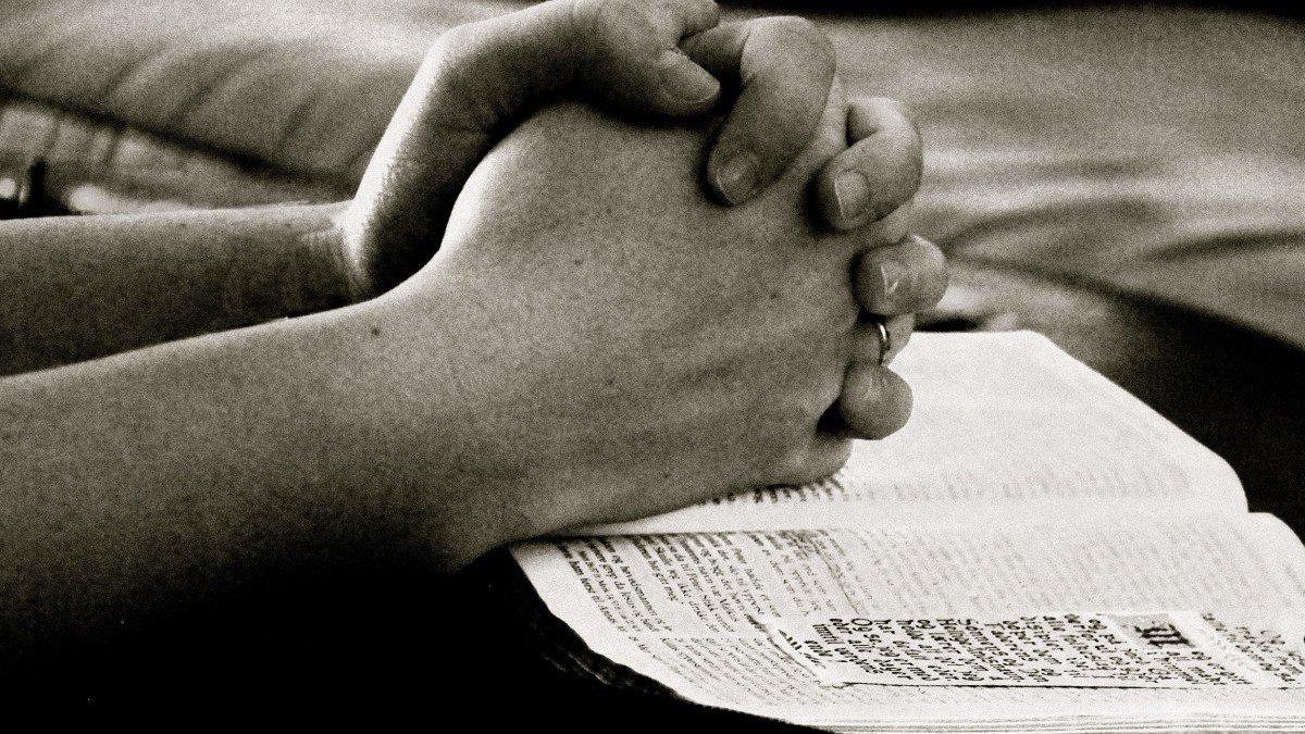 Mãos entrelaçadas em cima de uma Bíblia aberta